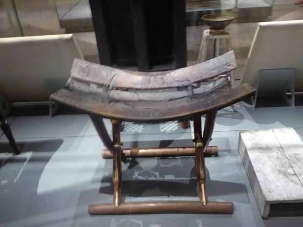127. Museo Egipcio. Silla plegable. Tumba de Kha. XVIII dinastía. Asiento en cuero y patas incrustadas con marfil y modeladas con cabezas de animales. Deir el-Medina